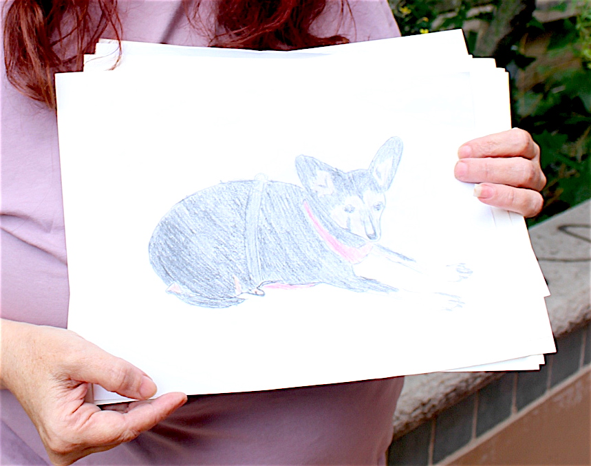 Sam, a resident at YWCA's Opportunity Place, holds a picture she made of a friend's pet. Sam says that creating art has built her confidence and helped her connect with community.